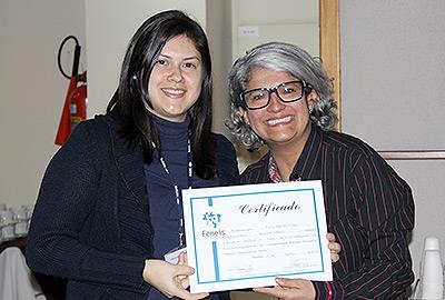Imagem em plano médio mostra servidora ao lado de professora do curso de Libras, recebendo seu certificado. Ambas olham para a câmera, enquanto exibem o certificado.