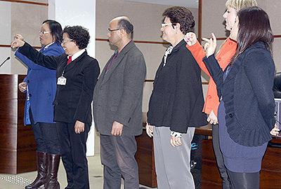 Imagem em plano geral mostra seis alunos que concluíram o curso de Libras, de pé, na parte da frente do auditório, dirigindo-se à plateia por meio de sinais.