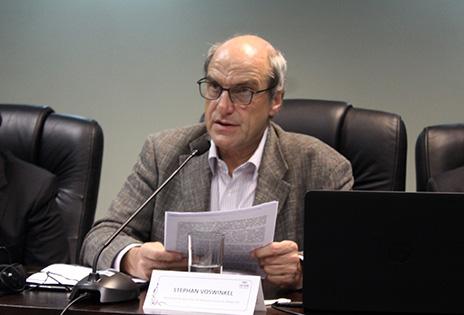 Imagem em plano médio mostra o jurista alemâo Stephan Woswinkel sentado à bancada do auditório da Escola Judicial, falando ao microfone para plateia de magistrados e servidores. O professor, usando óculos, está com um documento em mãos, como se estivesse fazendo uma leitura de algum trecho.