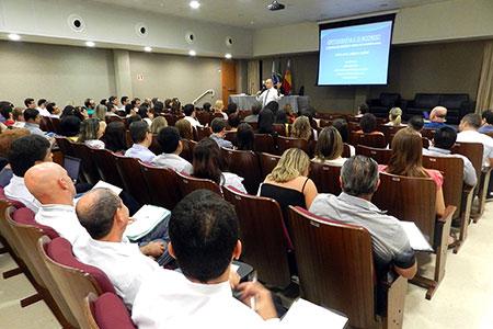 Foto em plano geral do auditório onde o evento foi realizado. A imagem traz os participantes do curso sentados enquanto o professor, de pé, na frente do auditório, fala ao microfone.