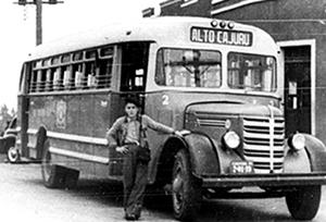 """Foto histórica traz trabalhador em frente a ônibus que tem como rota o """"Alto Cajuru""""."""