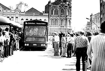 Foto histórica traz imagem frontal de um ônibus aguardado por uma grande fila de passageiros.