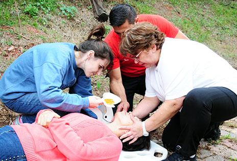 Imagem traz voluntários durante treinamento em situação de primeiros socorros.