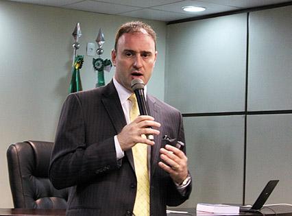Em plano médio, o advogado André Luiz Tesser palestrando. Ele segura um microfone. Atrás do palestrante, é possível ver a mesa principal do evento, sobre a qual estão dispostos alguns objetos, como um notebook. Ao fundo, pode-se ver a ponta de dois mastros e parte das bandeiras do Brasil e do Paraná.