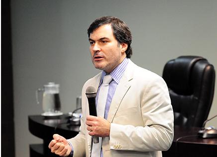Em plano médio, o professor Eduardo Talamini palestrando. Na mão esquerda, o docente segura um microfone. Atrás do palestrante, pode-se ver a mesa principal do evento, com alguns objetos.