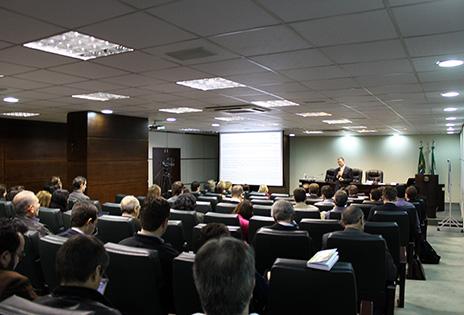 Em plano aberto, o auditório da Escola Judicial durante o evento. A foto foi tirada dos fundos do auditório. É possível ver a plateia e, ao fundo, um palestrante.
