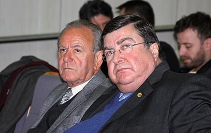 Fotografia em primeiro plano traz o ex-presidente do TRT-PR José Fernando Rosas e o ex-presidente nacional da OAB Roberto Busato na plateia da conferência