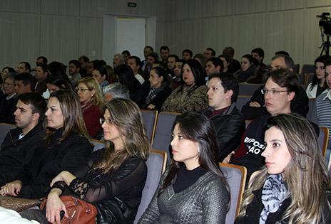 Fotografia em plano geral aberto traz a plateia do auditório ocupada pelos participantes