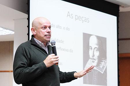 Professor Leandro Karnal, diante de tela, profere palestra.