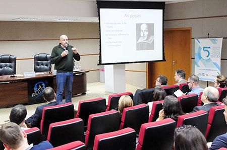 Imagem aberta mostra parte da plateia com o palestrante ao fundo