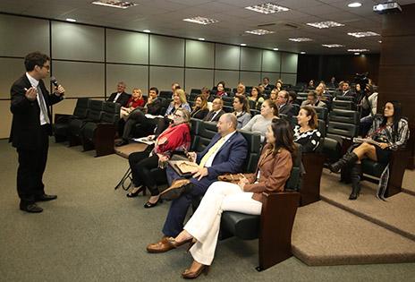 Imagem do auditório onde ocorreu o evento, com palestrante José Eduardo Romão e participantes.